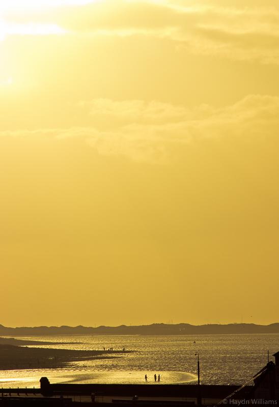 Sunset over the Menai Straits and the beach at Caernarfon.